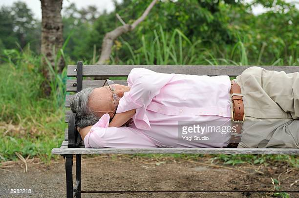 A senior's man is doing a nap with a bench.