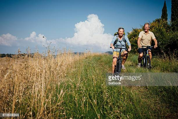 seniors on mountain bikes in the countryside - landelijke scène stockfoto's en -beelden