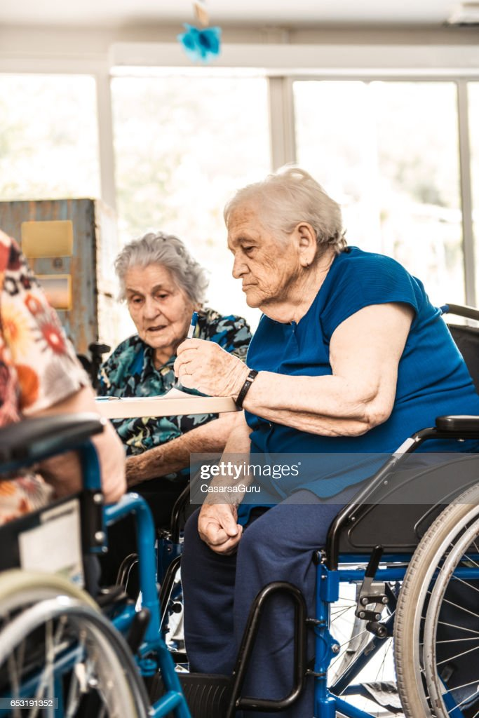 Seniors On The Wheelchair In The Nursing Home Waiting For The Therapy In The Gym Class : Stock Photo