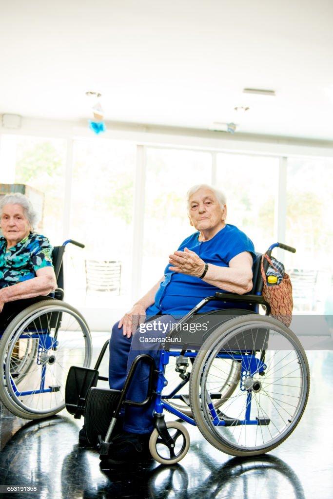Seniorer på rullstolen i vårdhem väntar terapin i klassen Gym : Bildbanksbilder