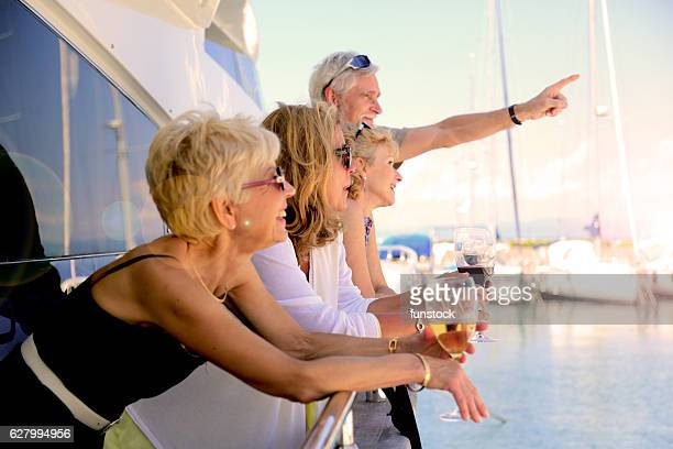 seniors on yacht observing the beauty of the summer sky - crucero vacaciones fotografías e imágenes de stock