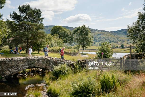 seniors out walking and crossing the river - cumbria stock pictures, royalty-free photos & images