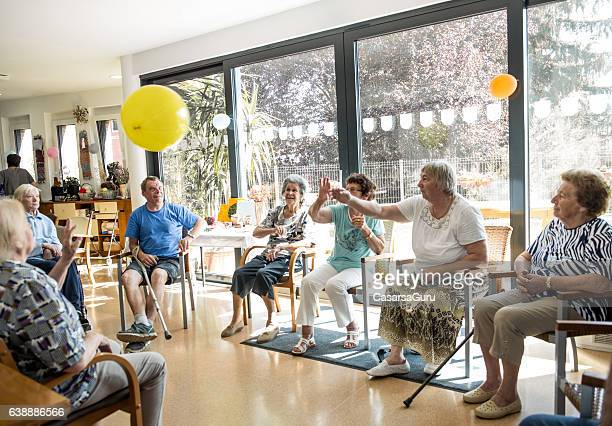 seniors participating in group activities in adult daycare center - activiteit stockfoto's en -beelden