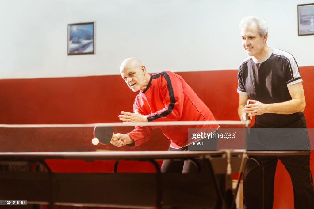 Seniors play table tennis : Stock Photo