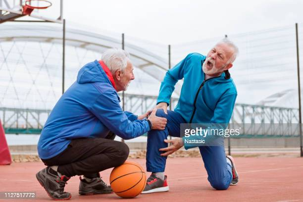 seniors playing basketball - knees together stock photos and pictures