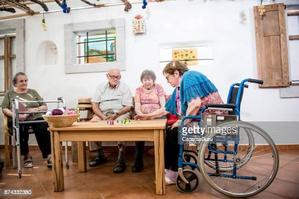 Senioren spielen Ludo im Innenbereich
