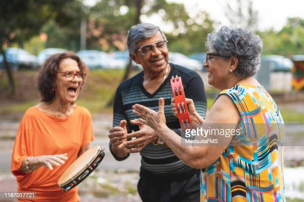 seniors playing the tambourine, singing and dancing in the public park - samba stock pictures, royalty-free photos & images