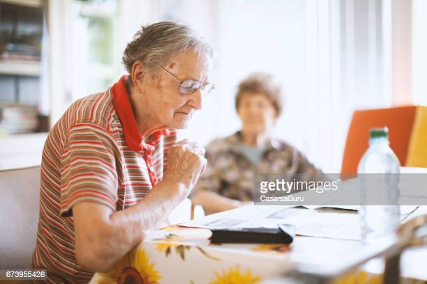 seniors reading newspaper  in the nursing home - residential care stock photos and pictures