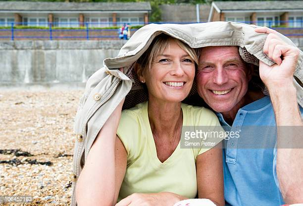 Seniors shelter under coat on beach