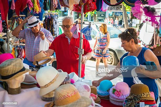 Seniors shopping for hats market stall El Rastro Madrid Spain