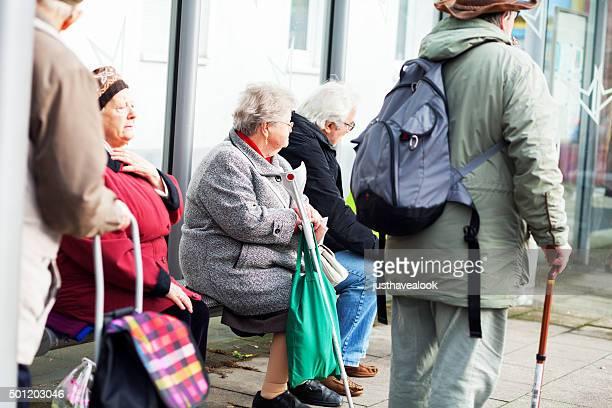 Les retraités assis dans un arrêt de bus