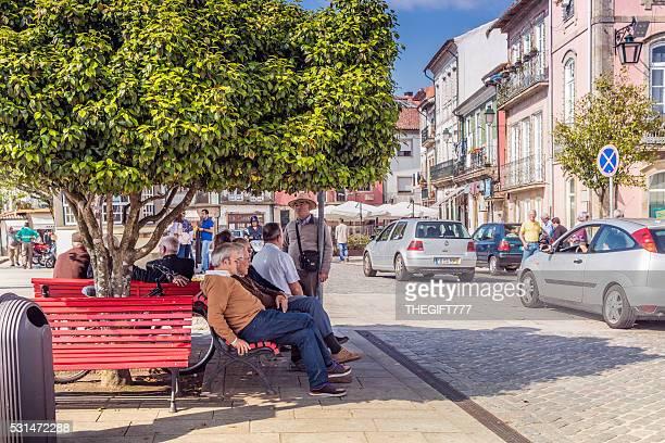 Seniores sentado sobre bancadas em uma árvore em Portugal