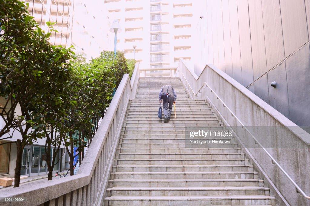 Seniors step up stairs : Stock Photo