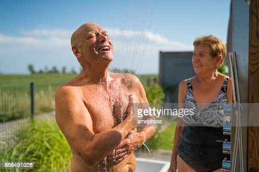 Seniors - taking a shower at home in garden