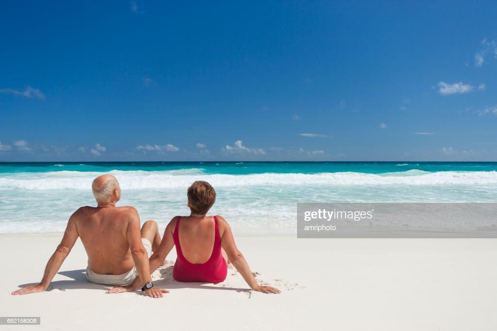 Seniors Taking on the World, back view couple sunbathing : Stock Photo
