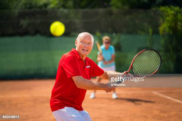 seniors taking on the world, happy senior man volleying on tennis net - tennis player stock pictures, royalty-free photos & images