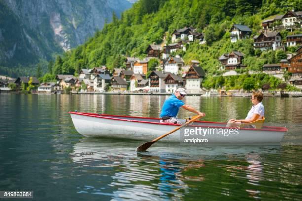 Senioren nehmen auf der Welt - älteres Paar im Ruderboot