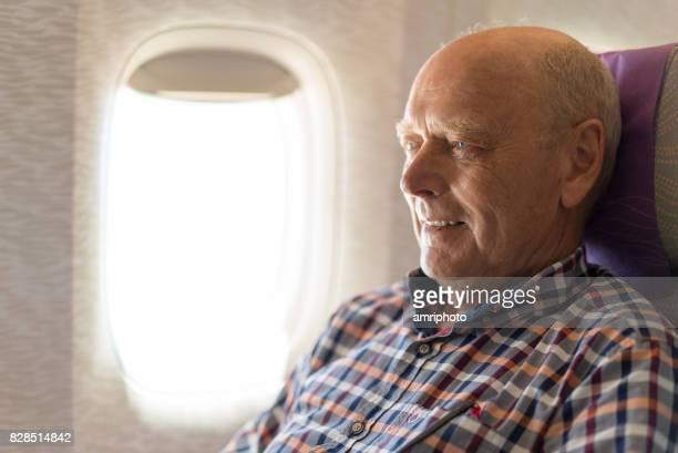 Senioren nehmen auf der Welt, lächelnd 72 Jahre alter Mann im Flugzeug am Fensterplatz