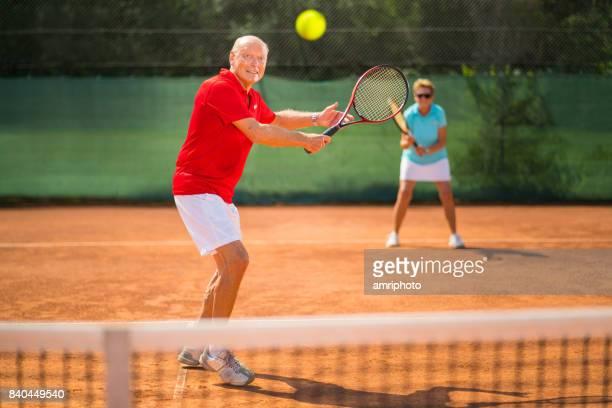 os idosos assumir o mundo, tenista senior sorridente focando a bola na rede - sporting term - fotografias e filmes do acervo