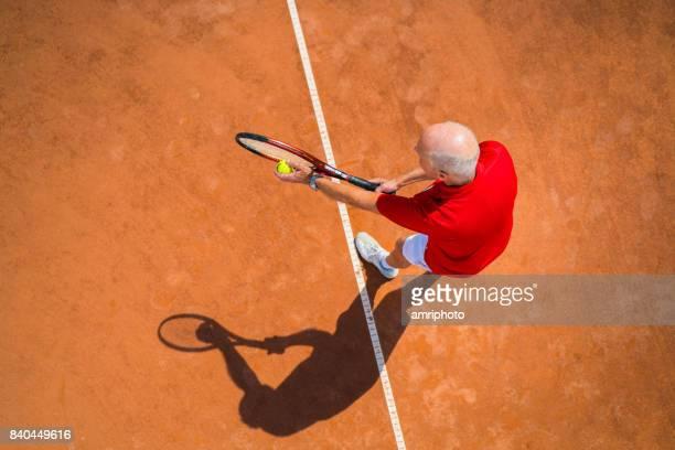 Seniors Taking on the World, top view senior man tennis service