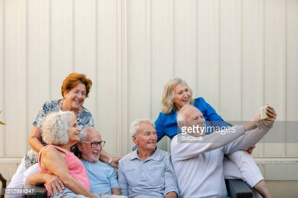 senioren, die selfies machen! - mittelgroße personengruppe stock-fotos und bilder