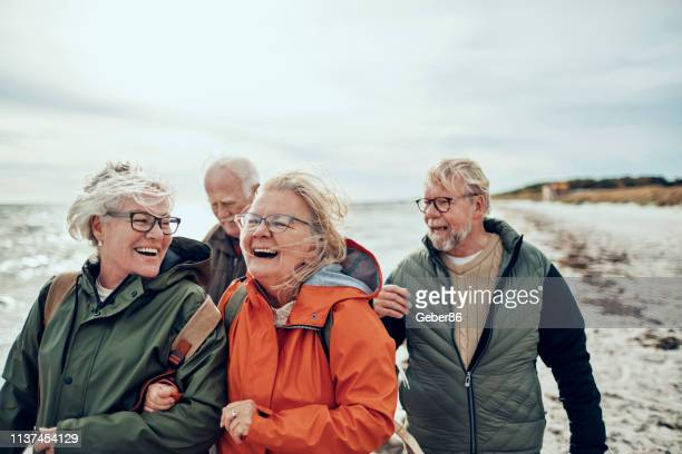 seniors walking on the beach - group of people stock pictures, royalty-free photos & images