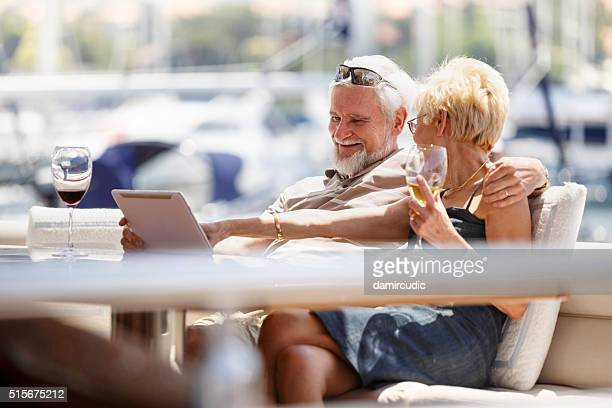 Seniour couple using digital tablet on a yacht