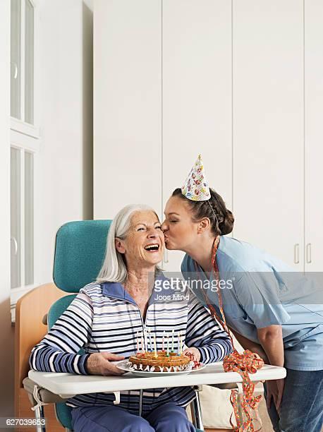 senir woman and caregiver celebrating birthday