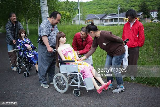 """Senji Nakajima shows his Love Doll """"Saori"""" to local residents, after the photo session with his friend at lake Suwa on June 4, 2016 in Nagano, Japan...."""