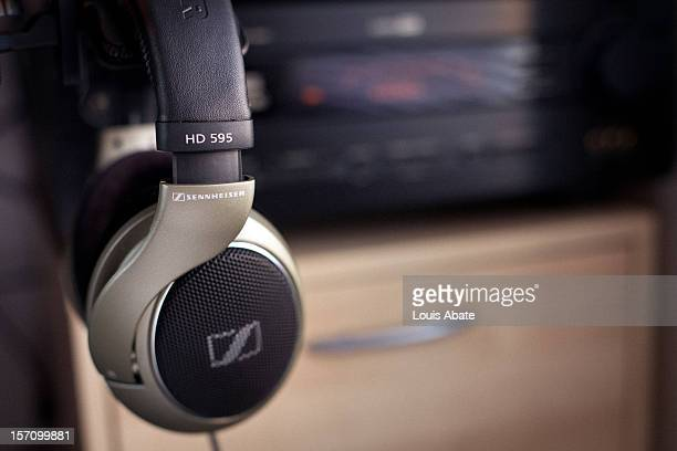 Sennheiser HD 595 Professional Headphones on their desk-mount holder. Side profile with model name clearly visible. Headphones are beige color with a...
