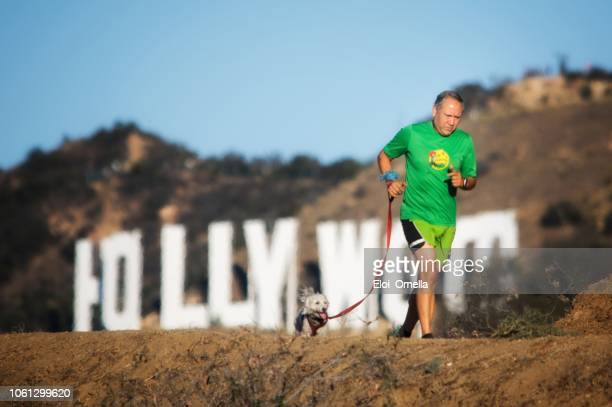 sennior man runing with dog in front of hollywood sign. los angeles. usa - hollywood califórnia imagens e fotografias de stock