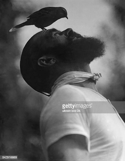 """Senor Costoya in Buenos Aires zähmte eine Lerche"""" - auf der Stirn eines Manne sitzt eine Lerche- um 1933Fotografie: Martin Munkascy"""