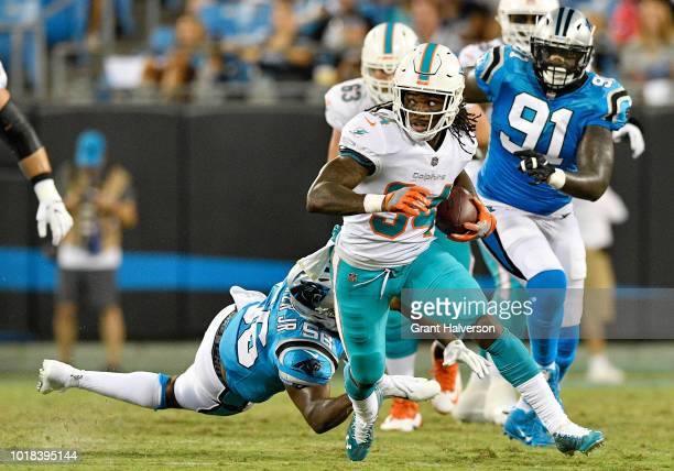 Senorise Perry of the Miami Dolphins runs the ball against the Carolina Panthers in the second quarter during the game at Bank of America Stadium on...