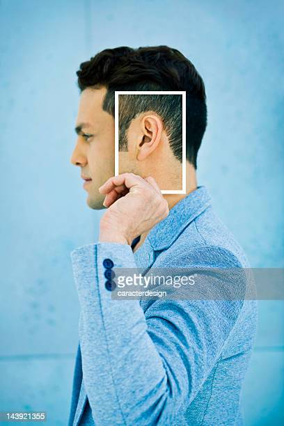 Senses: Man holding a photo of his ear