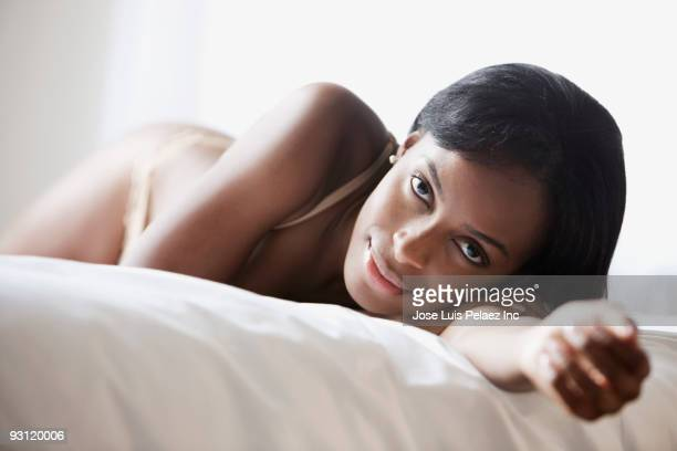 sensual african woman laying on bed - black sexual stock photos and pictures