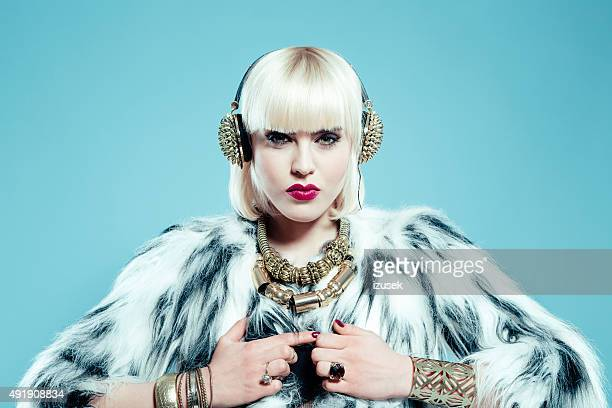 sensual blonde woman wearing fur jacket, gold jewlery and headphone - diva human role stock photos and pictures