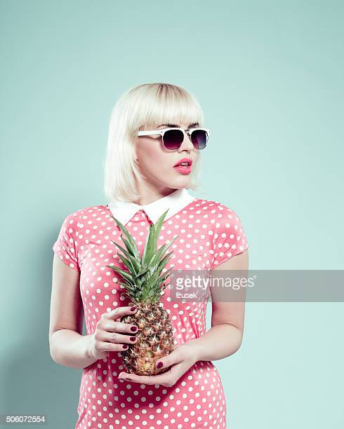 Sensual blonde young woman holding pineapple