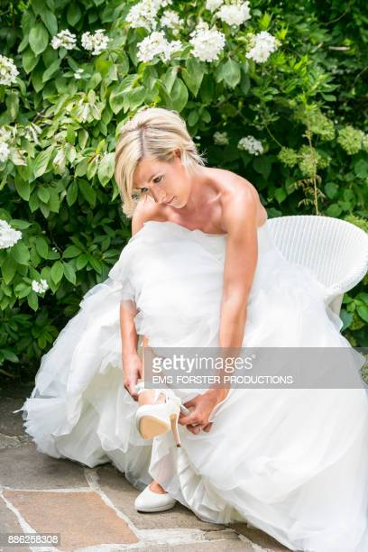 sensual bride in wedding dress on chair in front of green plants
