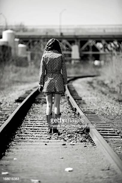 Sensual b&w image of a beautiful young woman standing isolated on a set of railroad tracks in an industrial urban area. She is faced away from the...