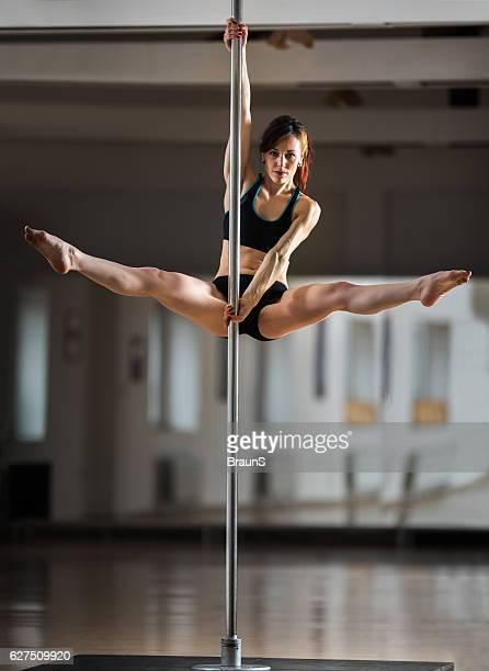 Sensual dancer exercising pole dancing in a studio.