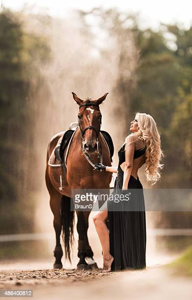 Sensual fashion model in black dress with a horse.