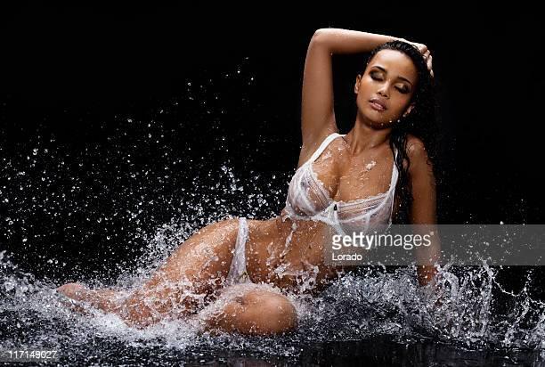 sensual fashion model posing in water splashes