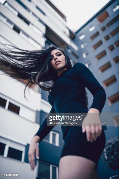 sensual female how spinning around with blown hair in city street - wind blowing up skirts stock photos and pictures