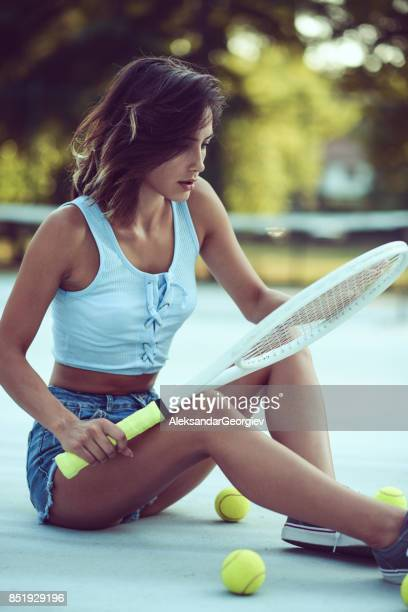 sensual female sitting on outdoor tennis court with racket - seductive women stock pictures, royalty-free photos & images