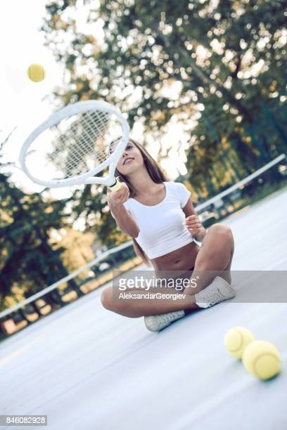 Sensual Female Sitting on Tennis Court Juggling with Racket And Ball