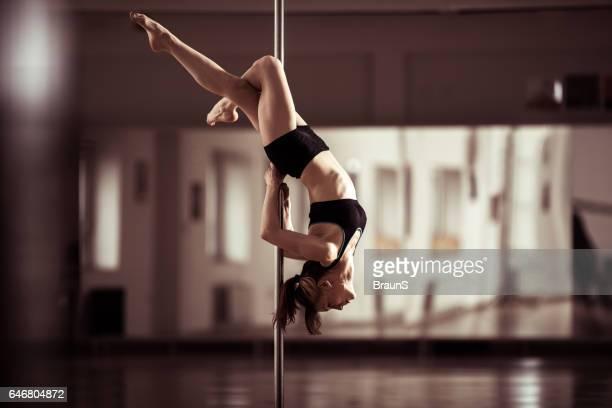 Sensual pole dancer dancing in a studio.