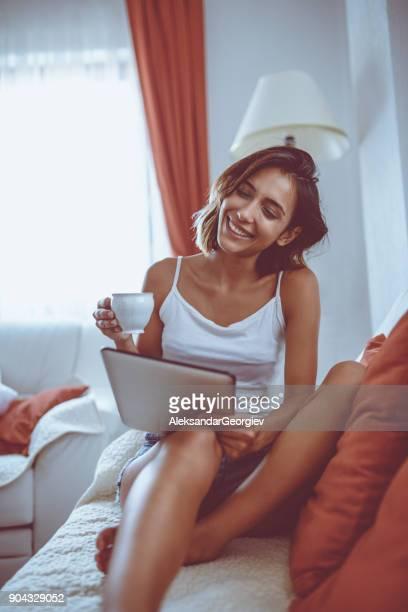 sinnliche lächelnde frau mit digital-tablette zu hause - digital desire fotos stock-fotos und bilder
