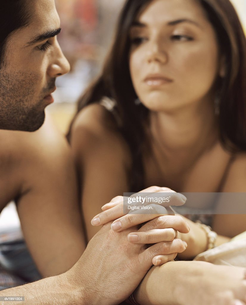 Sensual Twentysomething Couple Lying on a Bed Holding Hands : Stock Photo