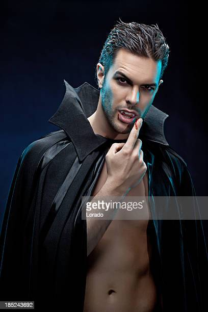 sensual vampire licking blood from his finger - vampire stock photos and pictures