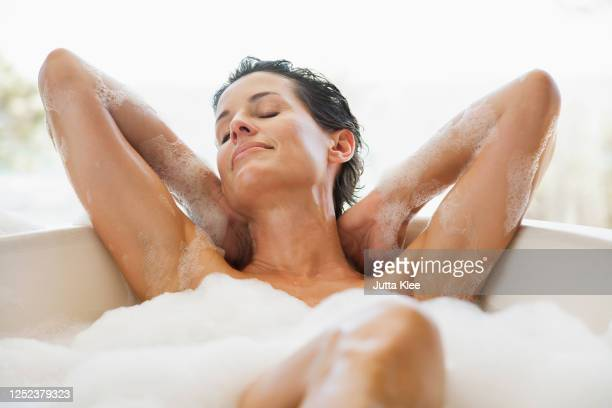 sensual woman enjoying bubble bath - wellness stock pictures, royalty-free photos & images